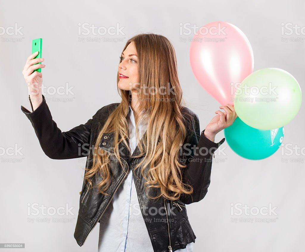 Chica modelo en estudio con globos hace autofoto foto de stock libre de derechos