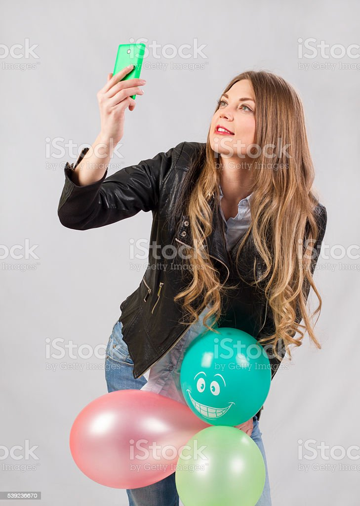 girl model in studio with balloons makes selfie royalty-free stock photo