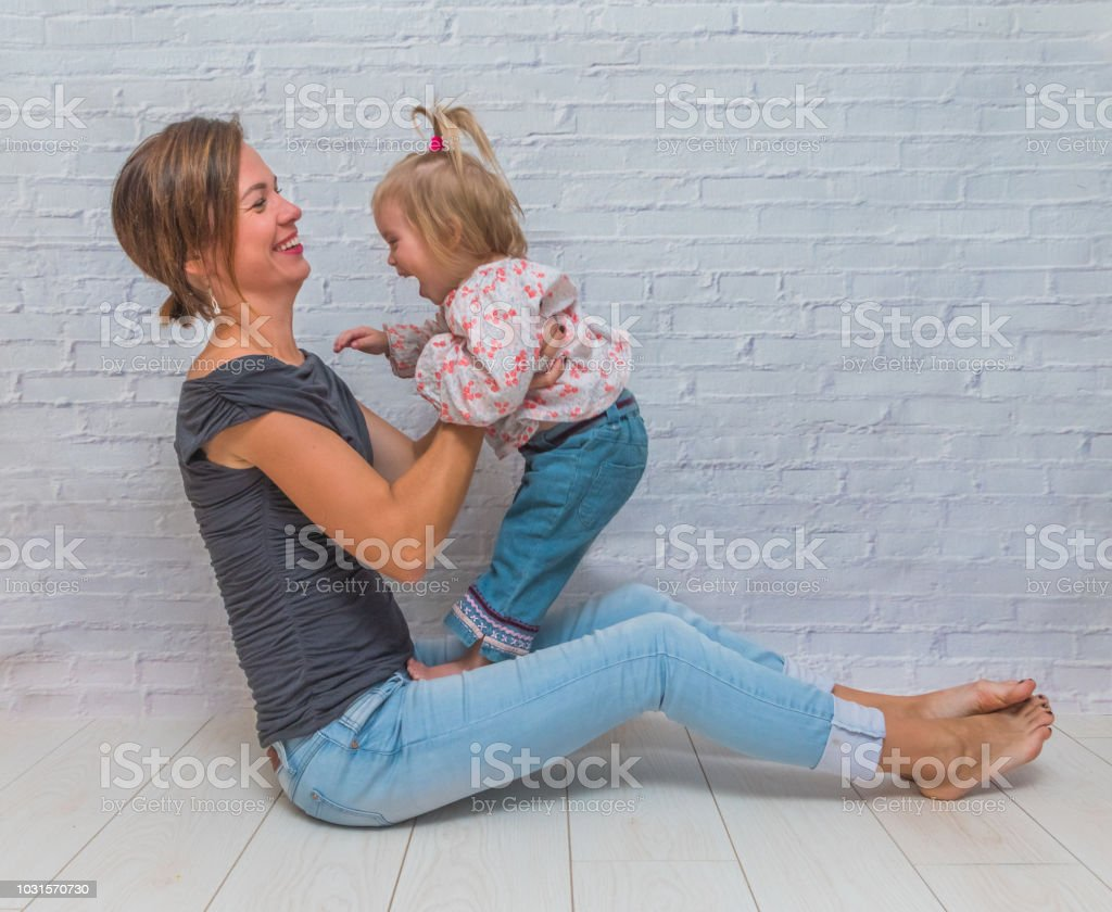 girl, mom and daughter, child on white brick wall background stock photo