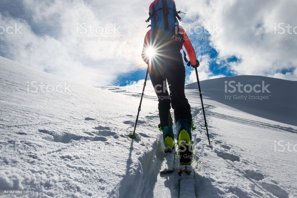 Girl mountaineer climb on skis and sealskins stock photo