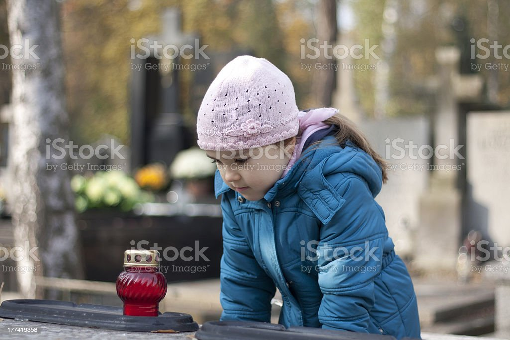 Girl mourning at the grave on cemetery royalty-free stock photo