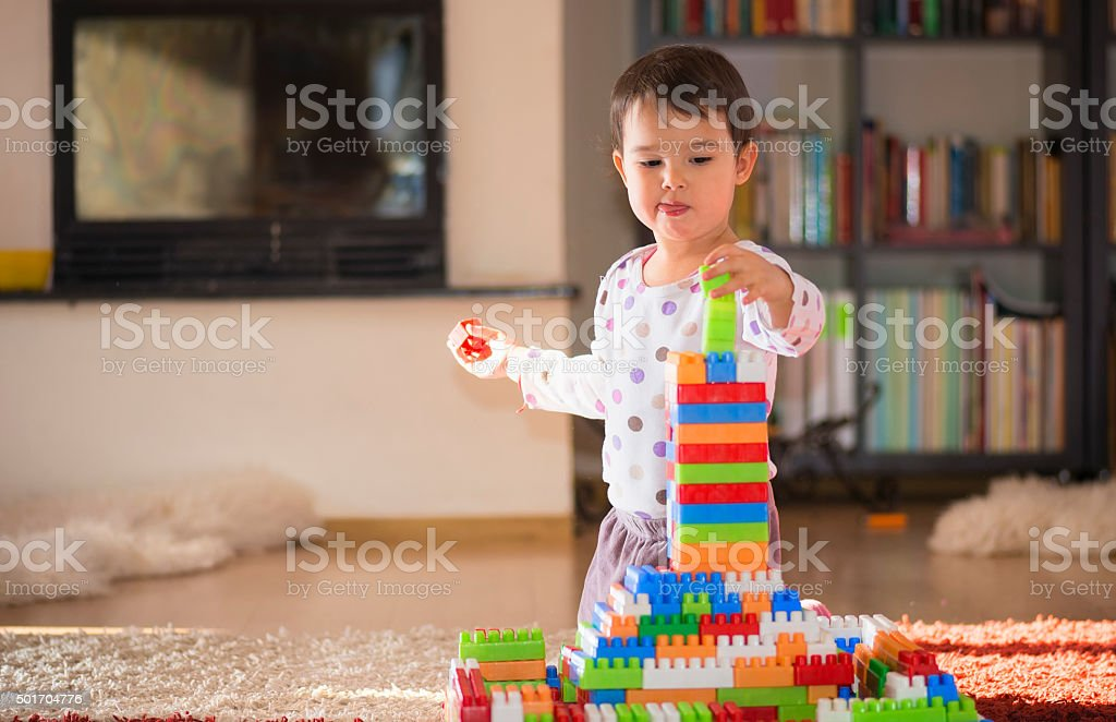 brunette girl of preschool age playing with colorful blocks sitting...
