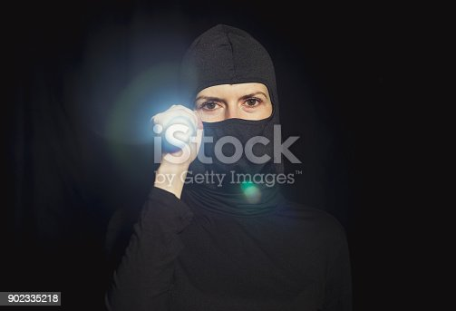 istock Girl offender. The girl in a black mask. 902335218