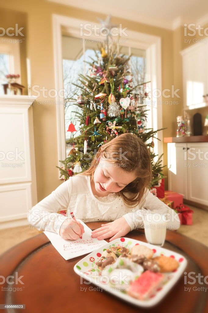 Girl Offering Cookies and Writing Christmas Wish List to Santa stock photo