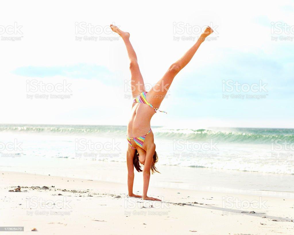 A girl on a beach doing a cartwheel stock photo