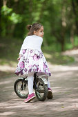 Four years old caucasian girl on her bike at sunny day in the park. Looking over her shoulder