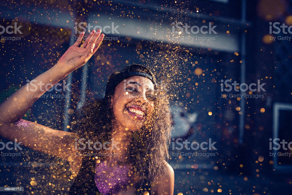 Girl on a city street throwing gold glitter in air stock photo