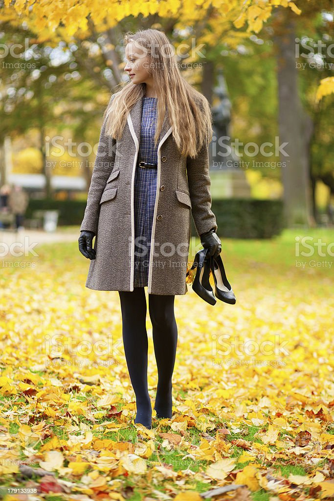 Girl on a fall day, with her shoes in hand royalty-free stock photo