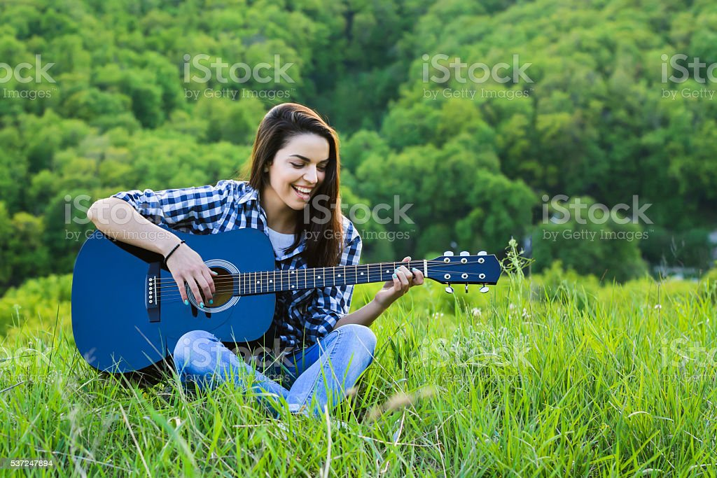 girl on a green meadow playing guitar stock photo