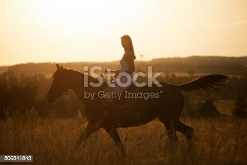 1128475475 istock photo Girl on a horse at sunset 506841843