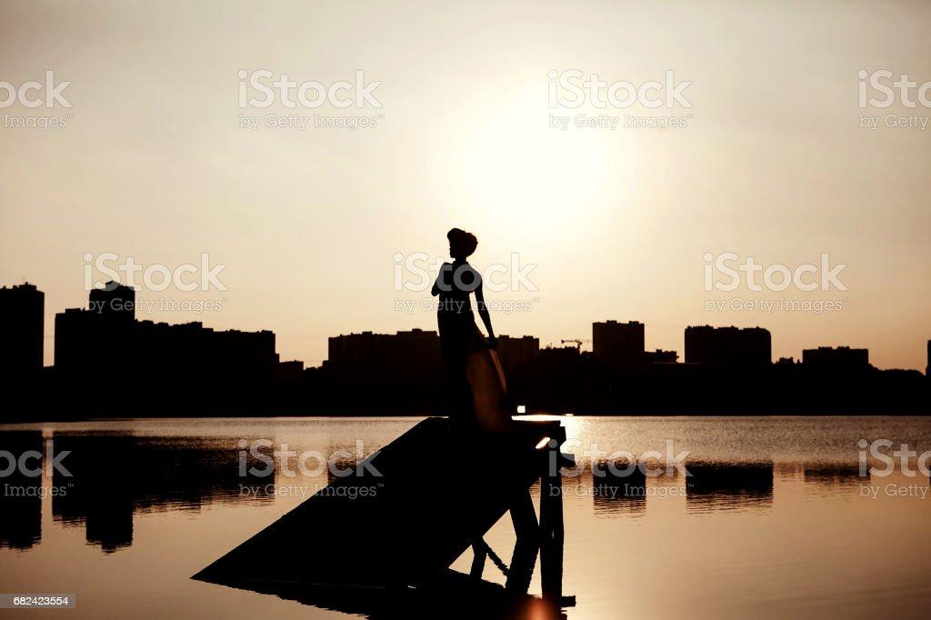 Mädchen auf einer Mole bei Sonnenuntergang silhouette Lizenzfreies stock-foto