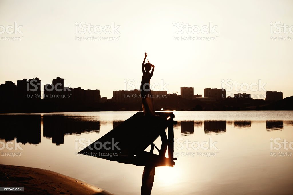 girl on a pier at sunset silhouette royalty-free stock photo