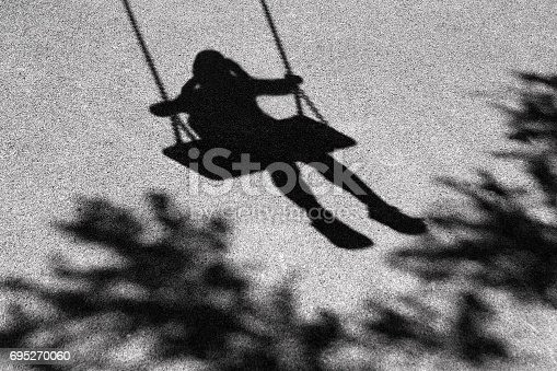 Blurry shadows of girl on a swing and a tree branch