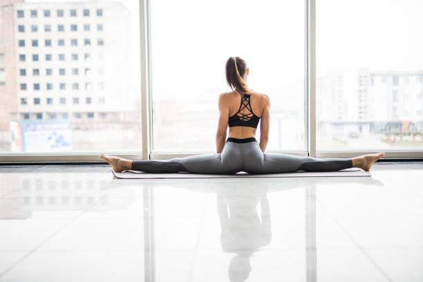 Flicka på ett snöre i en vit studio. Ung flicka öva yoga mot panoramafönster. Flickan på Garnets ser på kameran. bildbanksfoto