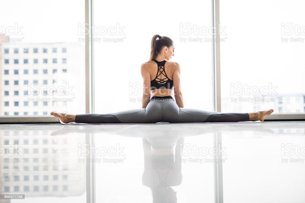 Garota em um barbante em um estúdio branco. Jovem praticando ioga contra janelas panorâmicas. A garota sobre a corda Olha para a câmera. - foto de acervo