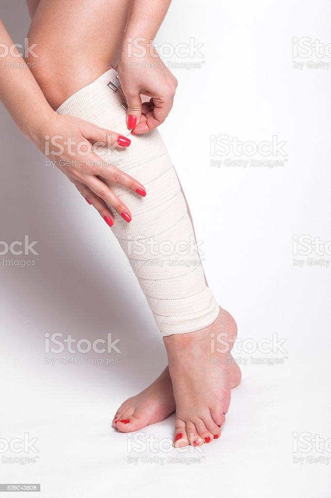 girl on a white background corrects an elastic bandage royalty-free stock photo
