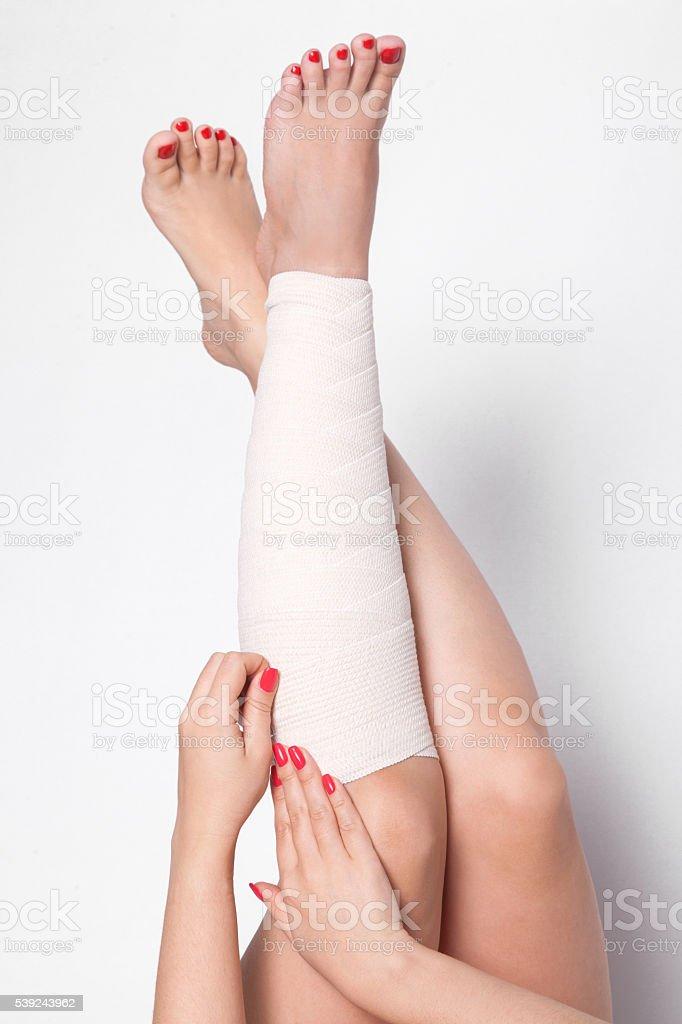 Garota em um fundo branco corrige uma faixa elástica foto royalty-free