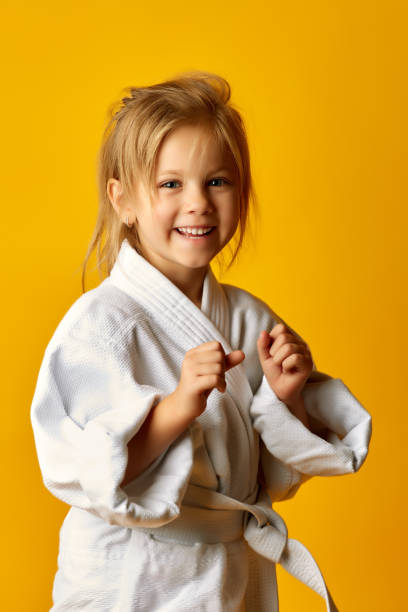 niña sobre un fondo amarillo con cinturón blanco golpea mano derecha - kárate fotografías e imágenes de stock