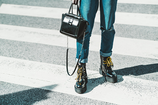 A close-up view of female legs in jeans and glossy boots with yellow laces - a woman standing on asphalt on the pedestrian zebra crosswalk with a small leather clutch in her hand on a sunny day