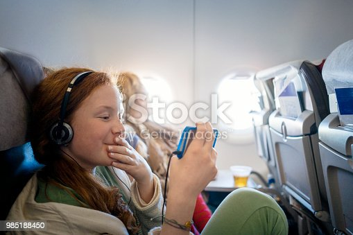 Girl sitting in an airplane passing time on her mobile phone watching a movie while waiting for landing
