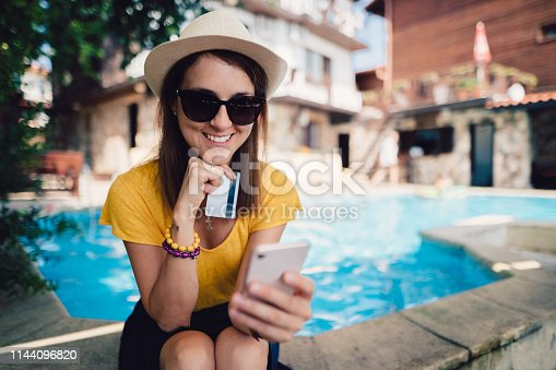 Woman sitting at the swimming pool and using credit card to make an online hotel reservation