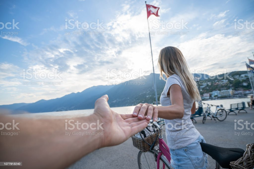 Girl on bicycle holding boyfriends hand leading him to the lake...