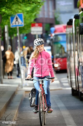 583973114istockphoto Girl on bicycle in traffic 476373402