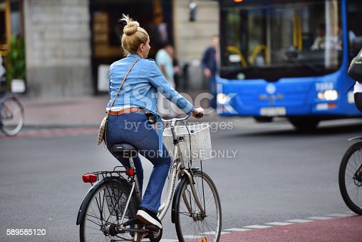 583973114istockphoto Girl on bicycle in traffic 589585120