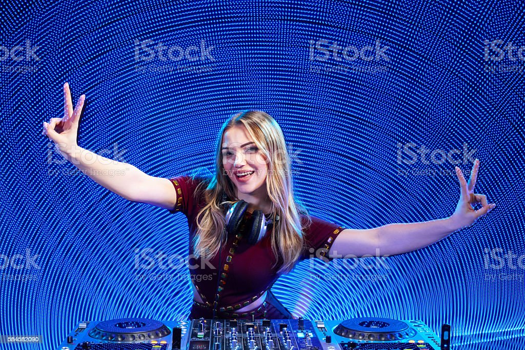 DJ girl on decks at the party gesturing V sign stock photo