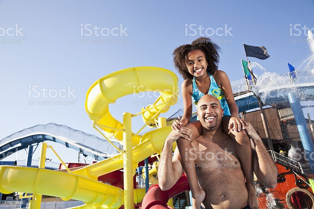 Girl on father's shoulders at water park stock photo