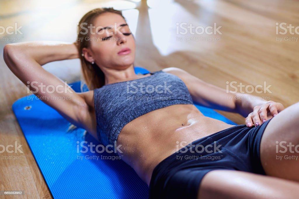 Chica en el piso haciendo ejercicios en el estómago en el gimnasio.  B húmedo - foto de stock