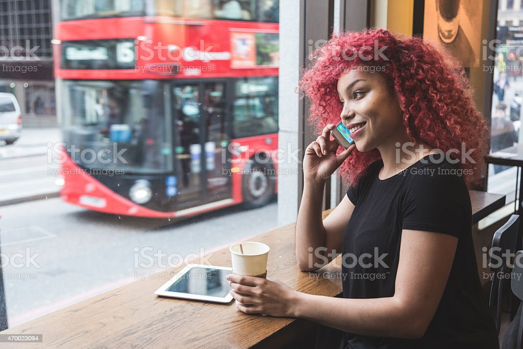 A girl on her phone at a cafe with coffee stock photo