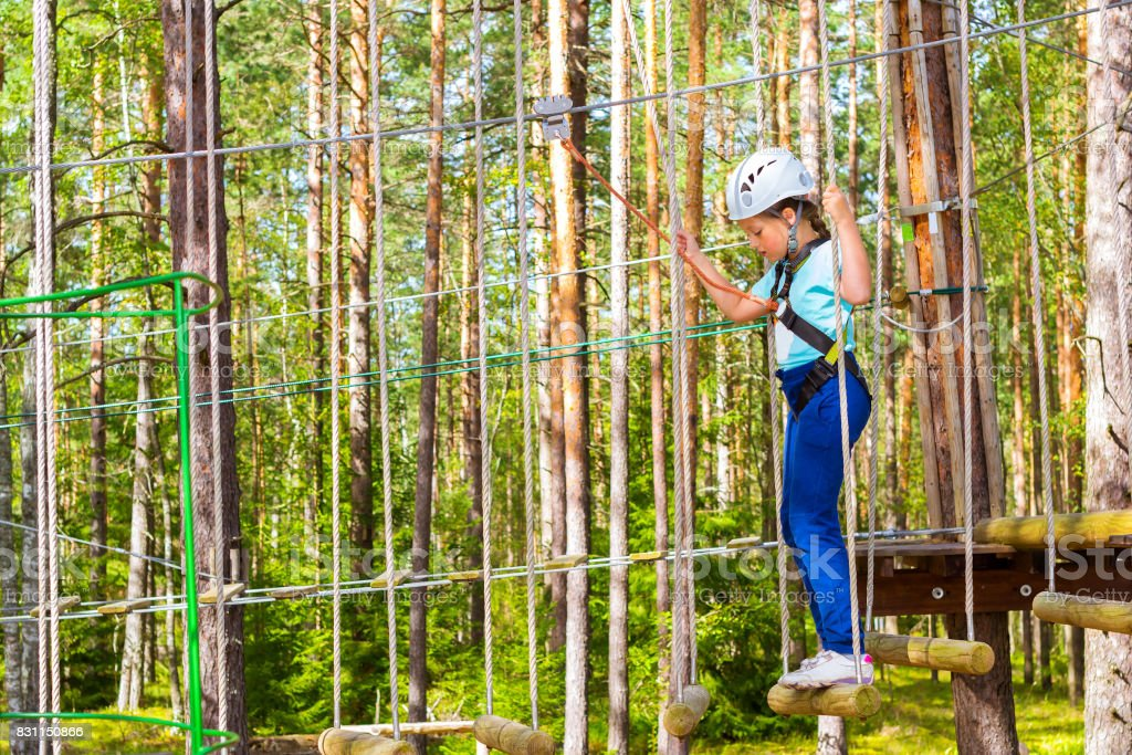 Girl on hinged trail in extreme rope Park stock photo