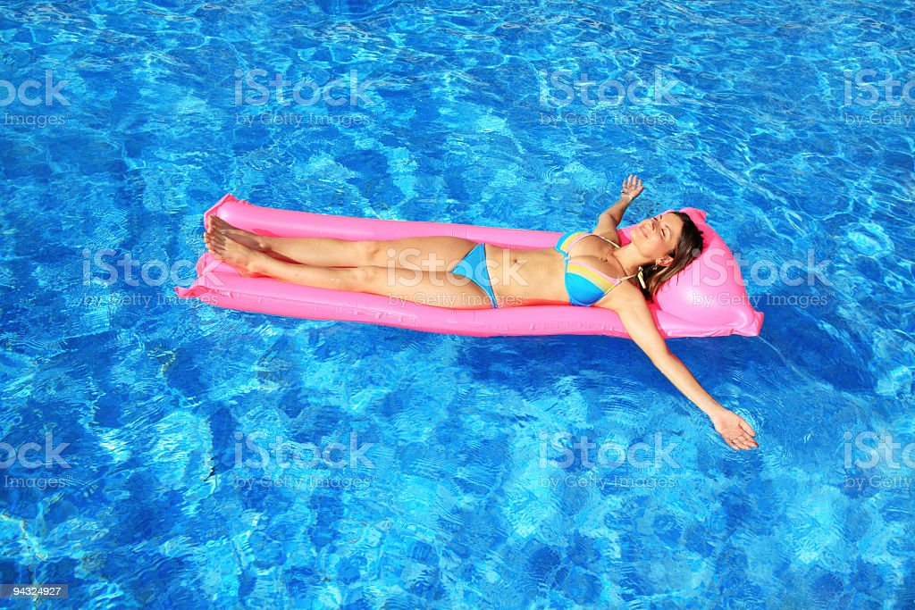 Girl on lilo floating in blue pool royalty-free stock photo