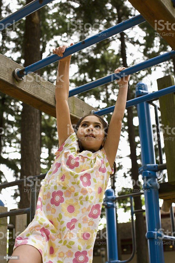 Ragazza sulla scala orizzontale/Struttura per arrampicarsi foto stock royalty-free