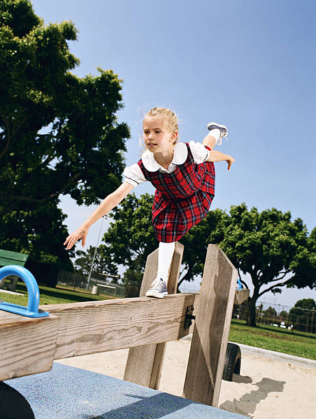 Girl (8-10) on playground, balancing on seesaw like gymnast stock photo