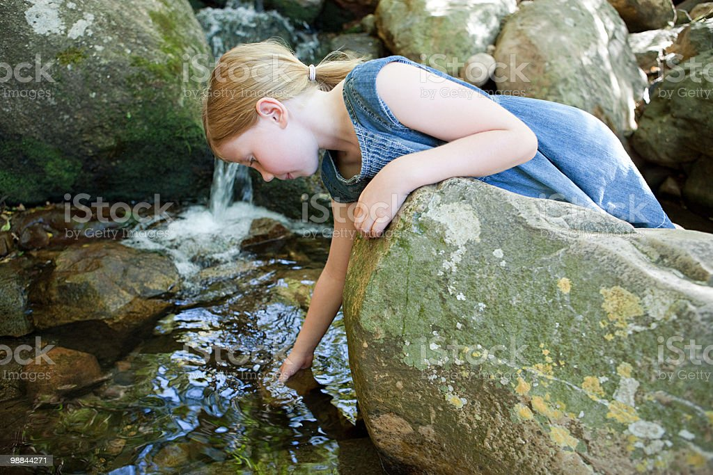 Girl on rock by river 免版稅 stock photo