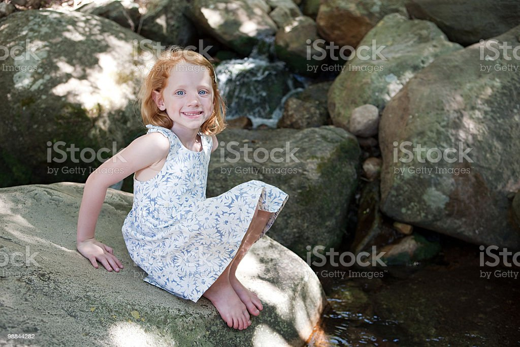Girl on rocks by river royalty free stockfoto