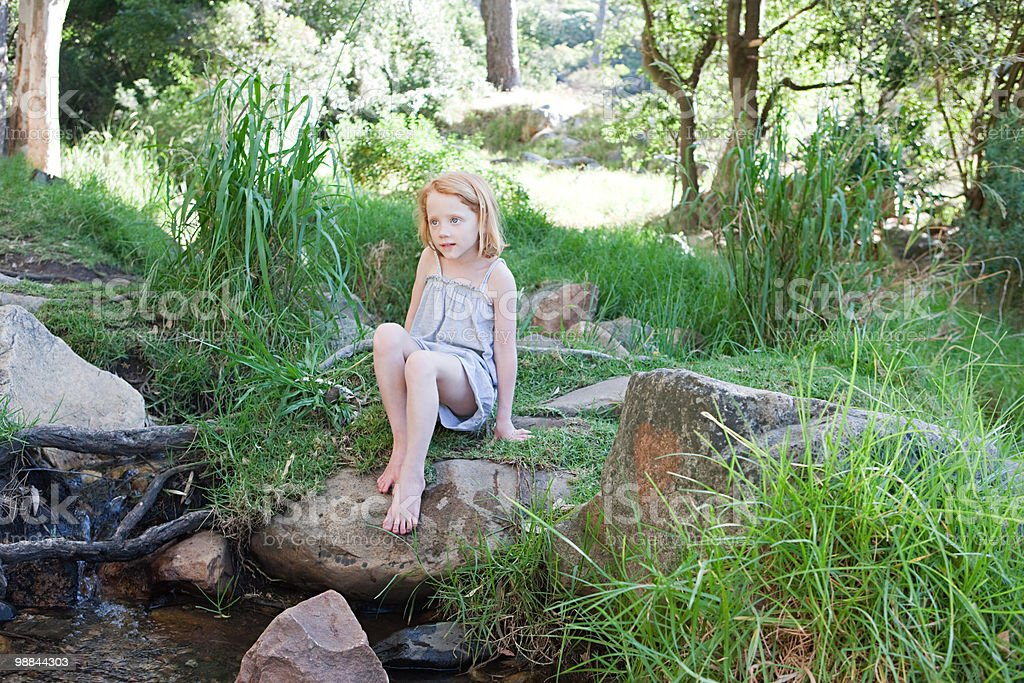 Girl on rocks by river royalty-free stock photo