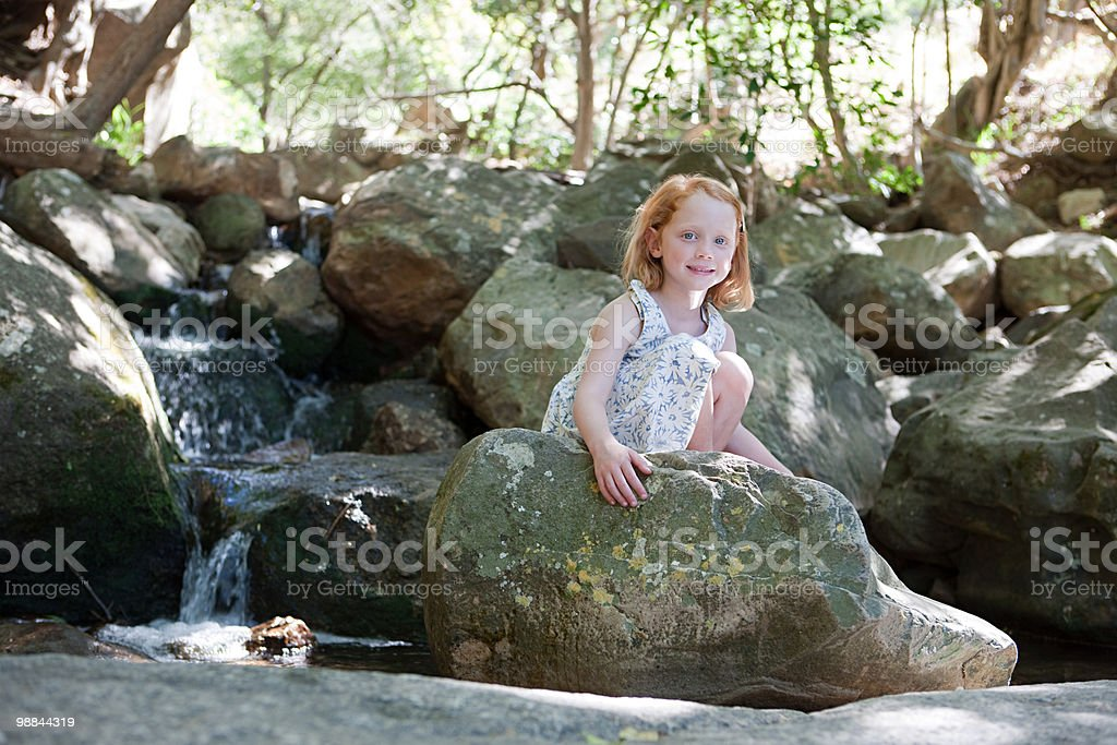 Girl on rocks by river foto royalty-free