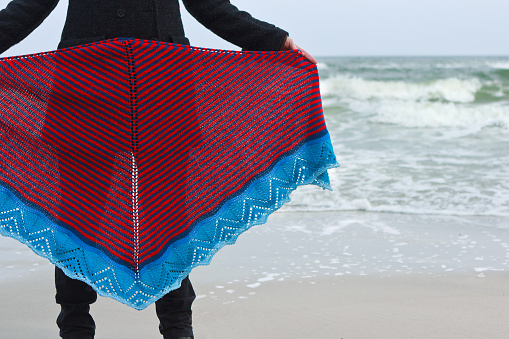 Girl on sea beach shows knitted shawl