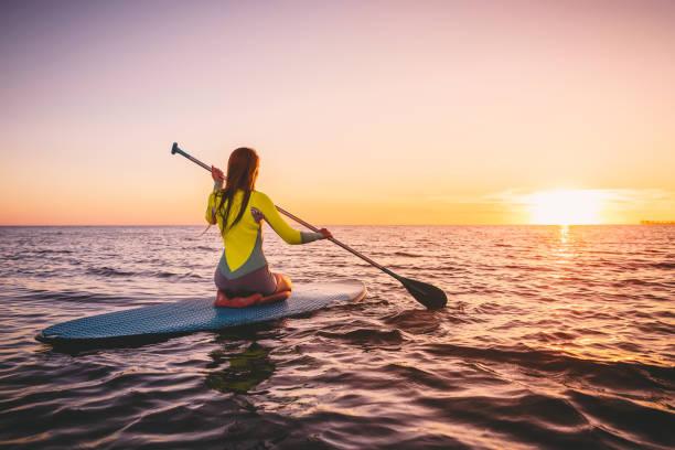 mädchen auf stand up paddle board, ruhige see mit warmen sonnenuntergang farben. entspannung am meer - stehpaddeln stock-fotos und bilder