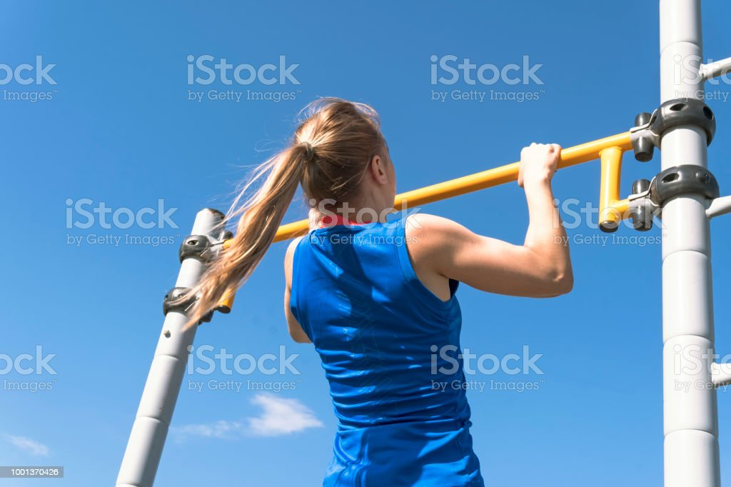 Girl on street workout. She pull-ups herself up on bar on sports ground in park. Photo from the back. Man is unrecognizable stock photo