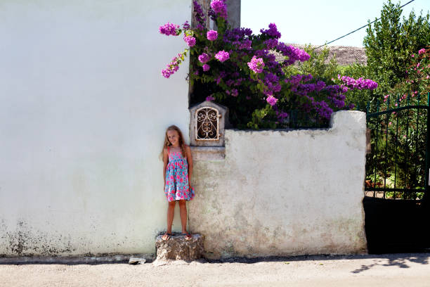 girl on summer vacation posing by the house full of flowers - tamara dragovic stock photos and pictures