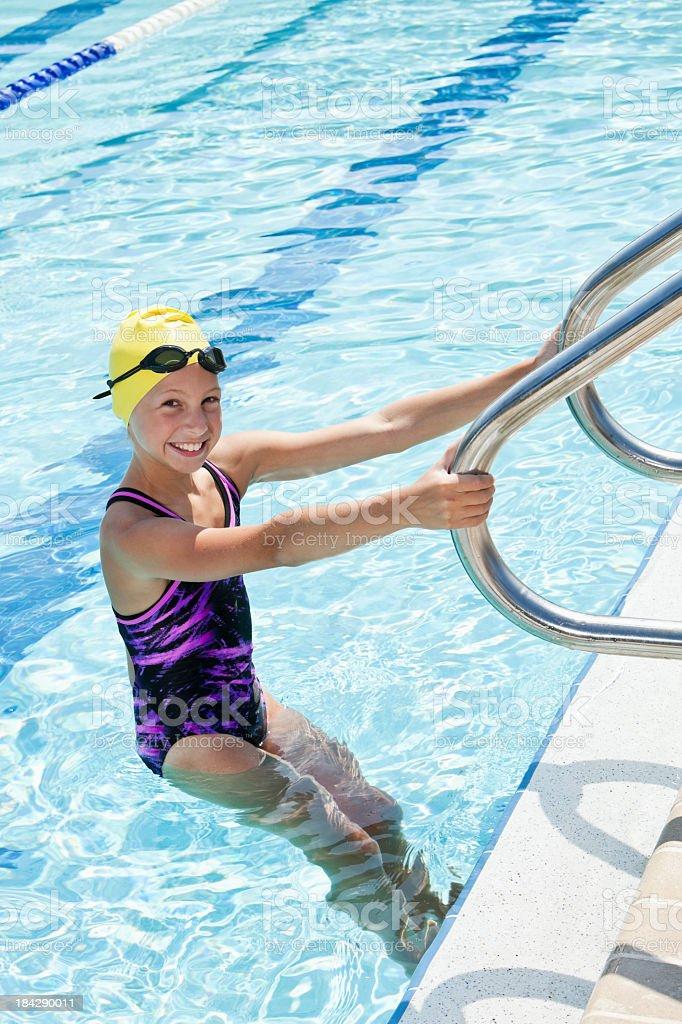 Girl on swimming pool ladder stock photo