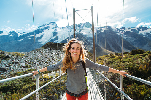 Beautiful girl on a swing bridge on the Hooker Valley trail on the South Island of New Zealand.