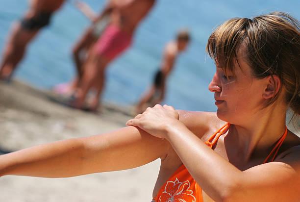 Girl on the beach applying suntan lotion to her shoulders stock photo