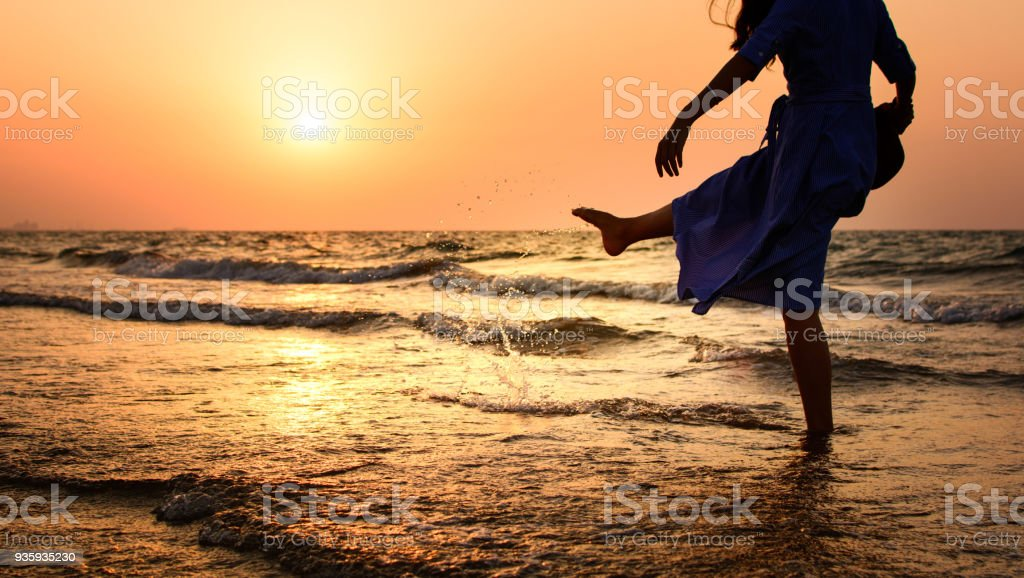 Girl on the beach at sunset stock photo