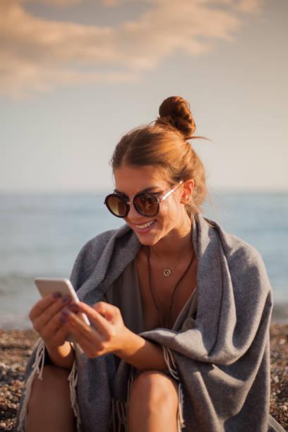 Chica en la playa con teléfono - foto de stock