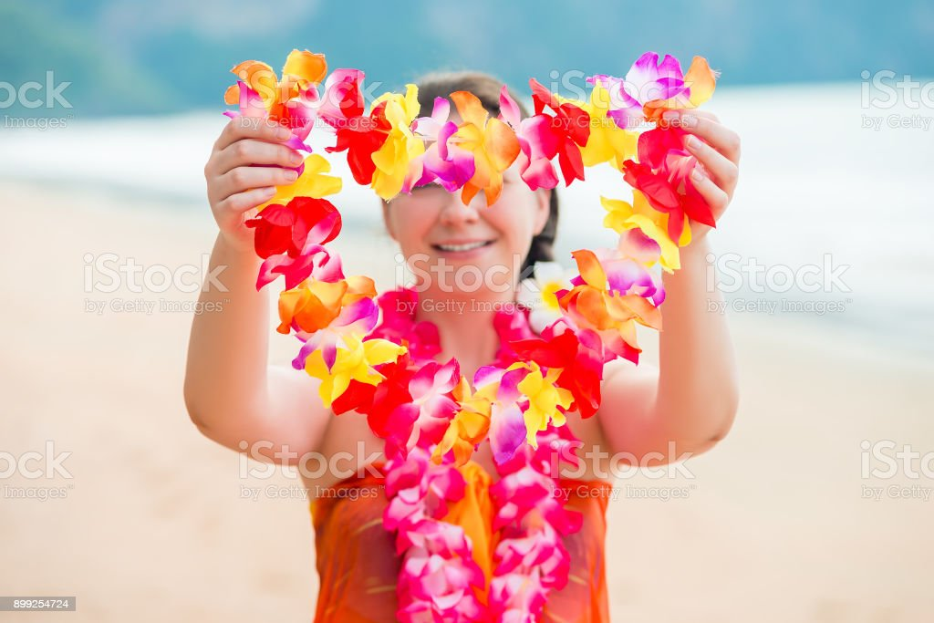 Girl on the beach welcomes guests with floral Lei traditional Hawaiian stock photo